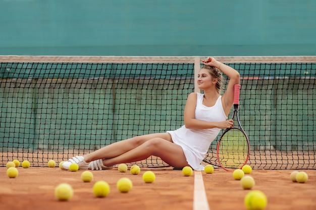 テニストレーニングの後にリラックス。ネットの近くのテニスコートに横たわっている白い制服とスポーティな帽子の若い美しい少女。