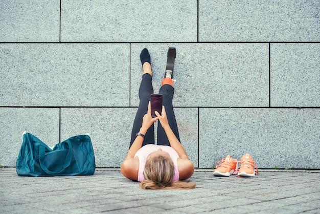 Расслабляющий после тренировки вид сверху женщины с протезом ноги в спортивной одежде, держащей ее