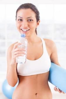 운동 후 휴식. 스포츠 클럽에 서 있는 동안 물과 운동 매트가 든 병을 들고 스포츠 의류를 입은 쾌활한 젊은 여성