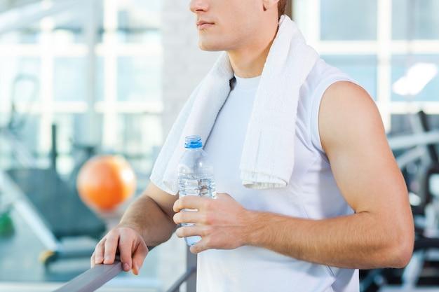 Расслабление после тренировки. обрезанное изображение молодого человека с полотенцем на плечах и питьевой водой, стоя в тренажерном зале