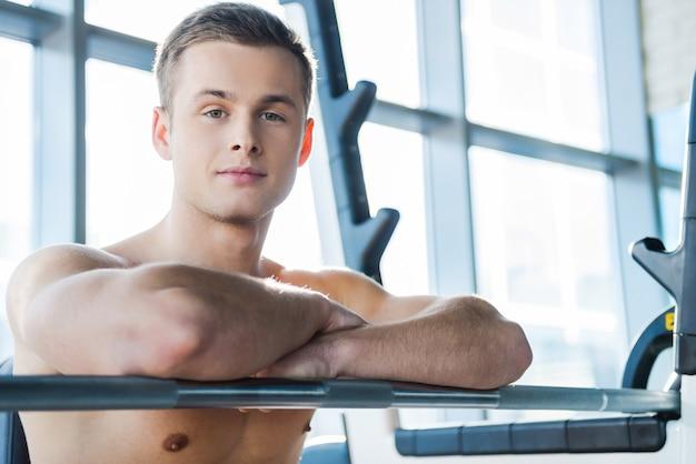トレーニング後にリラックス。ベンチプレスに座っている間、腕を組んでカメラを見ているハンサムな若い筋肉の男