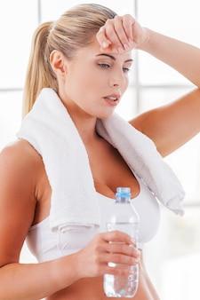 トレーニング後にリラックス。水でボトルを保持しながら手で額に触れるスポーツ服で疲れた成熟した女性