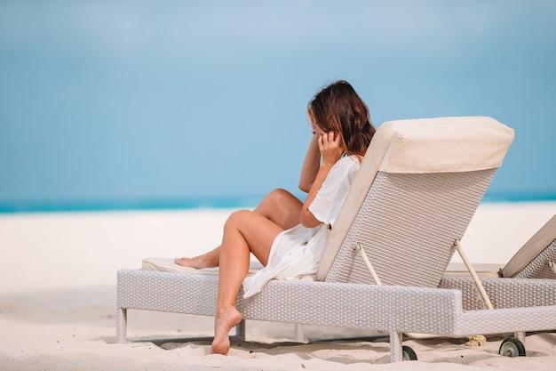 夏休みにリラックスして楽しんで、ビーチでサンベッドに横たわっている女性