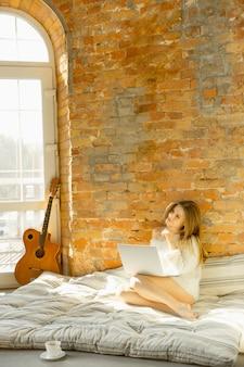 집에서 휴식. 따뜻한 햇빛과 매트리스에 누워 아름 다운 젊은 여자. 금발 여성 모델은 휴식을위한 주말 시간이 있습니다.