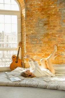 家でリラックス。暖かい日光の下でマットレスの上に横たわっている美しい若い女性。白人の金髪モデルは休憩のための週末の時間があります