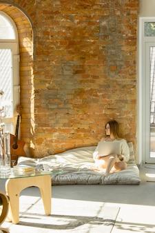 家でリラックス。暖かい日光の下でマットレスの上に横たわっている美しい若い女性。