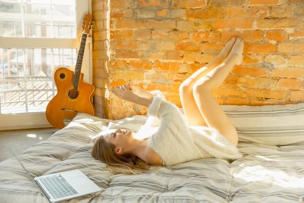 Отдыхаете дома. красивая молодая женщина, лежа на матрасе с теплым солнечным светом.