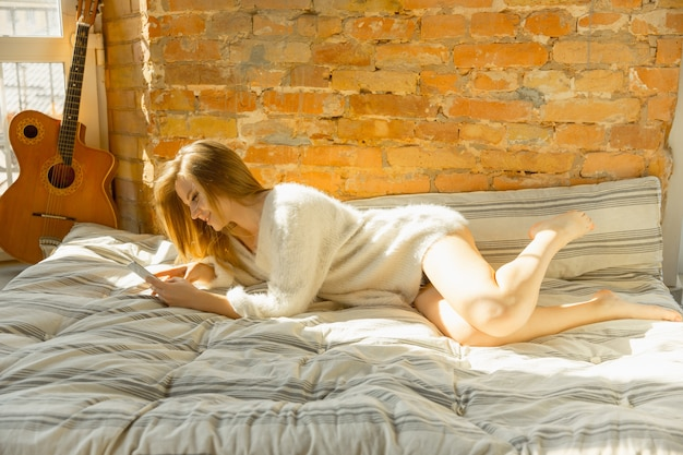 家でリラックス。暖かい日光とマットレスの上に横たわって美しい若い女性