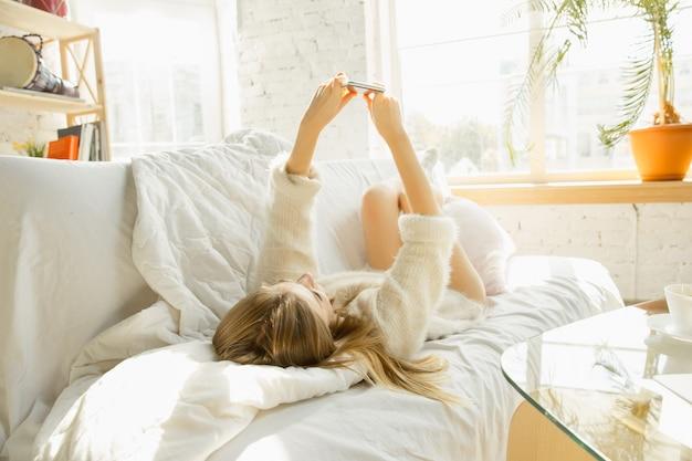 家でリラックス。暖かい日差しの中で自宅のソファに横たわっている美しい若い女性。
