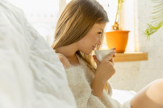 家でリラックス。暖かい日光とソファに横たわって美しい若い女性