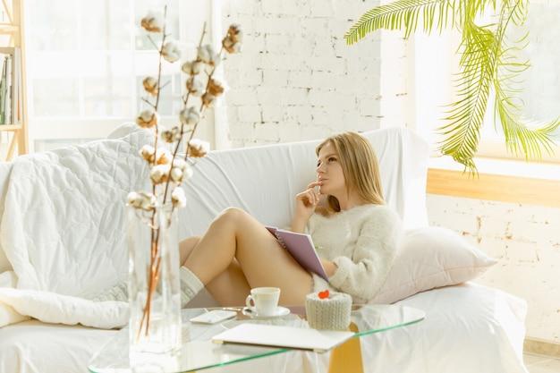 집에서 휴식. 따뜻한 햇빛으로 소파에 누워 아름 다운 젊은 여자