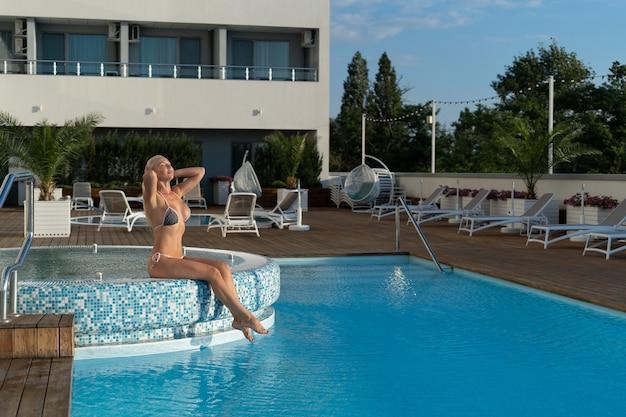 Расслабляющий в отеле у бассейна и расслабляющая блондинка сидит на краю. санаторий или
