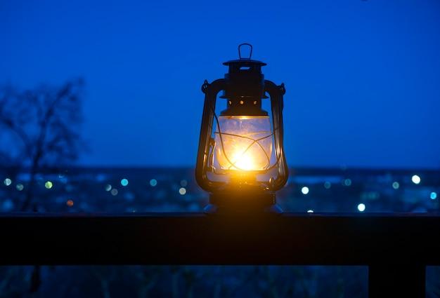 ボケ味の風景に対してテーブルの上の古代の灯油ランプでリラックスした背景。