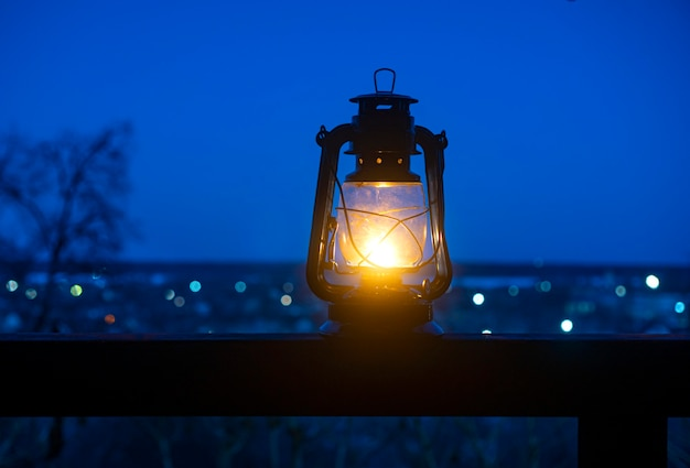 Relaxing background with ancient kerosene lamp on the table against the landscape with bokeh.