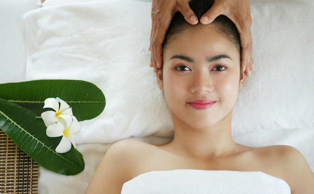 Relaxing beautiful asian woman having a massage skin on a face in spa salon.