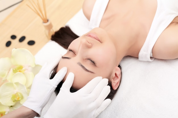 Relaxing beautiful woman having a massage for her skin on a face in beauty salon