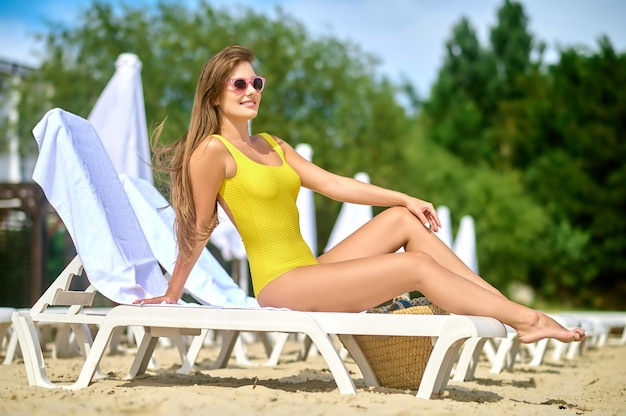 Relaxing. a beautiful young woman in a yellow swimming suit sunbathing and feeling great