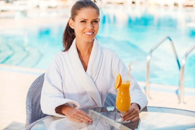 Relaxing by the pool. beautiful young woman in bathrobe holding cocktail and smiling while sitting at the table by the pool