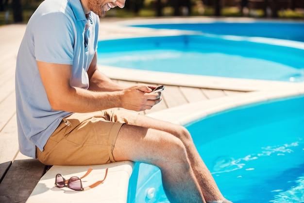 수영장에서 휴식. 폴로 셔츠를 입은 젊은 남자가 풀사이드에 앉아 휴대전화로 무언가를 입력하는 모습