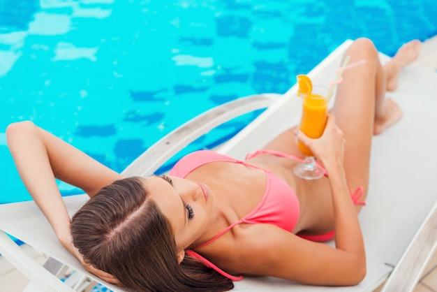 수영장에서 휴식. 수영장 옆 갑판 의자에서 휴식을 취하는 동안 칵테일을 들고 비키니를 입은 아름다운 젊은 여성의 상위 뷰