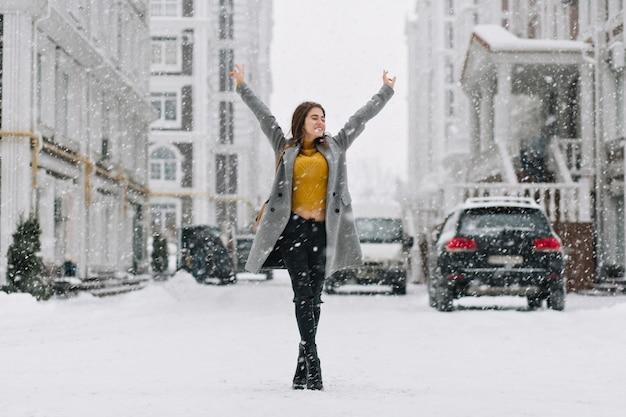 白人女性が都市通りの降雪の下で手でポーズをとってリラックスします。冬の町で週末を楽しんでいる黄色いセーターとグレーのコートを着たきれいな女性の屋外フルレングスの写真。