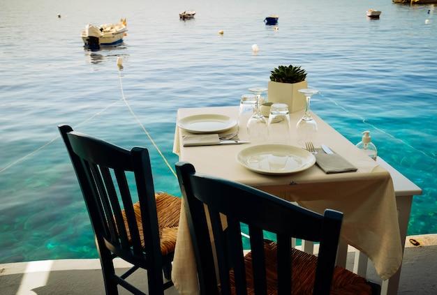 ギリシャ、サントリーニ島のカルデラを望むリラックスできる椅子とディナーテーブル