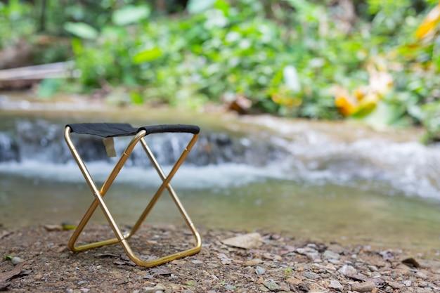 편안한 의자가 강 옆에 있습니다.