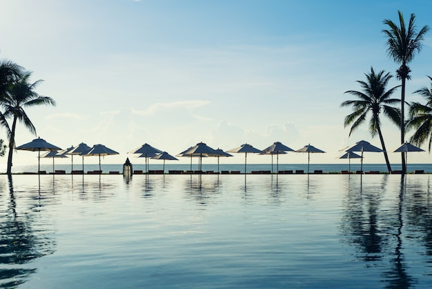 Relaxing chairs beside of swimming pool near sea in luxury resort or hotel.