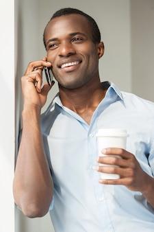 Расслабление во время перерыва на кофе. веселый молодой африканец в голубой рубашке держит чашку кофе и разговаривает по мобильному телефону