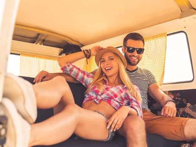 Отдыхая во время поездки. веселая молодая пара смотрит в камеру и улыбается, сидя на задних сиденьях своего минивэна