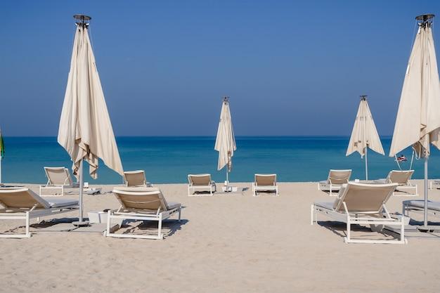태양 침대, 바다 풍경과 함께 편안한 빈 해변. 여름 휴가 여행 휴가 개념.