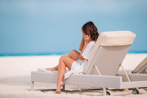 Relaxing and enjoying on summer vacation, woman lying in sunbed on beach