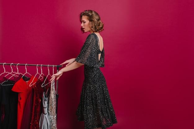 Ragazza rilassante in abito nero scegliendo un vestito per il servizio fotografico