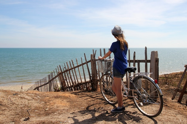 Relaxing girl with bicycle standing on the sea
