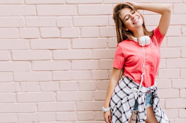 체크 무늬 셔츠와 흰색 손목 시계가 눈으로 포즈를 취하는 편안한 소녀는 벽돌 벽 앞에서 폐쇄