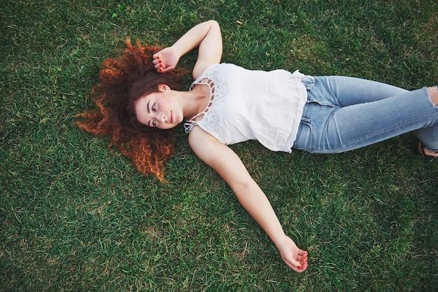 Ragazza rilassante con rosso, sdraiato sull'erba.