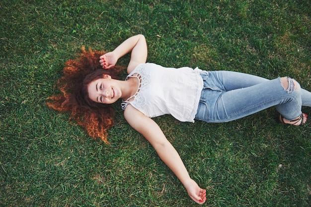 草の上に横たわる赤でリラックスした女の子。