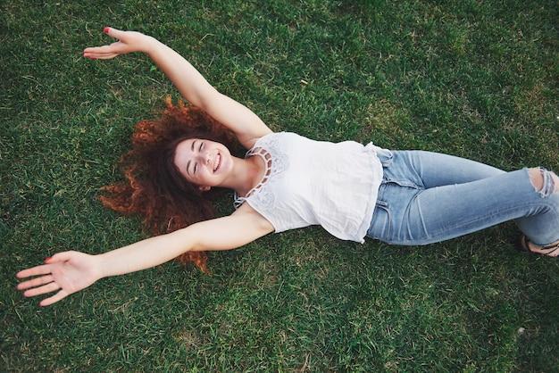 Расслабляющий девушка с красным, лежа на траве.