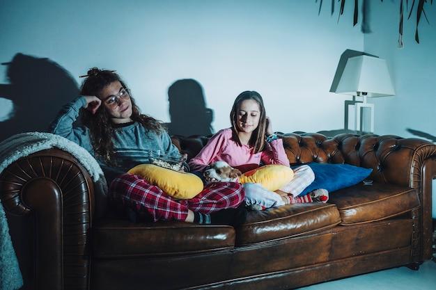 Расслабляющие девушки с собакой на диване