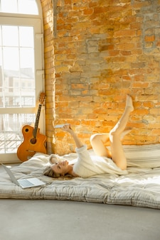 Relaxing at home. beautiful young woman lying on mattress with warm sunlight.