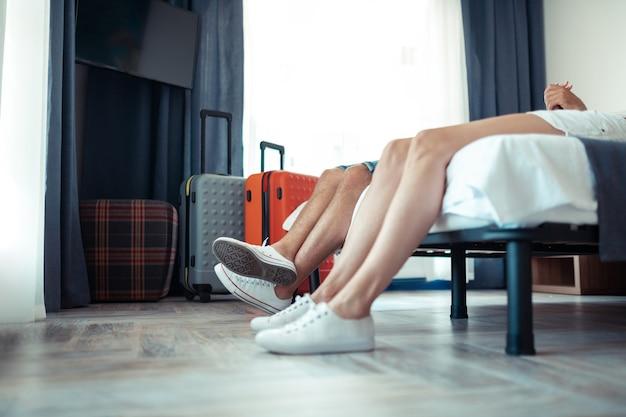 Отдых в отеле. ноги супружеской пары, лежащей на кровати в гостиничном номере в первый день отпуска.