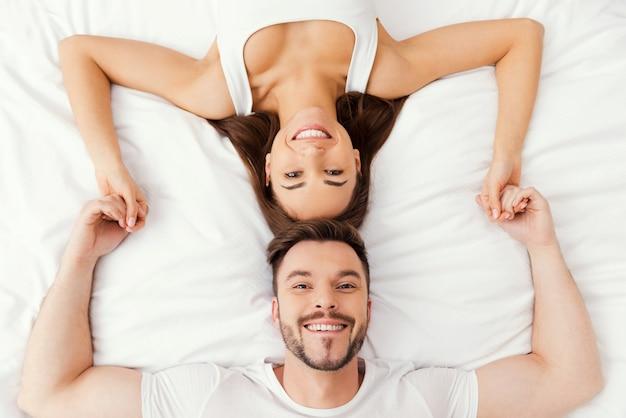 Вместе расслабляйтесь в постели. вид сверху красивой молодой влюбленной пары, лежа в постели вместе и взявшись за руки