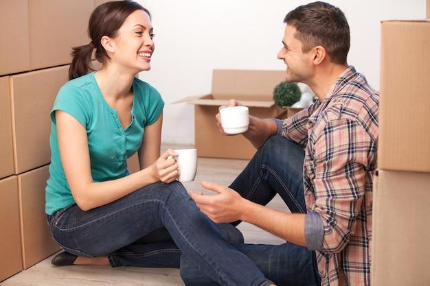 Отдых в новом доме. веселая молодая пара сидит на полу и пьет кофе, а вокруг них лежат картонные коробки