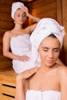 Отдых в сауне. две привлекательные женщины, завернутые в полотенце, расслабляются в сауне и с закрытыми глазами