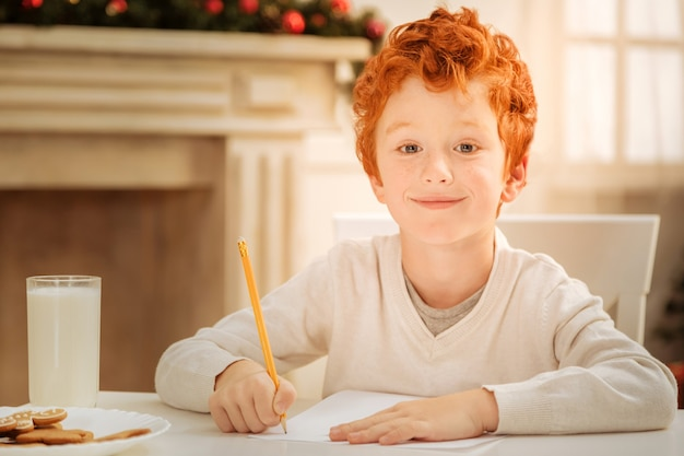 Relaxing leisure activity. positive minded ginger child with a cheerful smile on his face while enjoying tasty food and drawing at home.