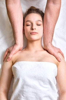 Relaxing massage top view woman receiving shoulders and neck massage at spa salon
