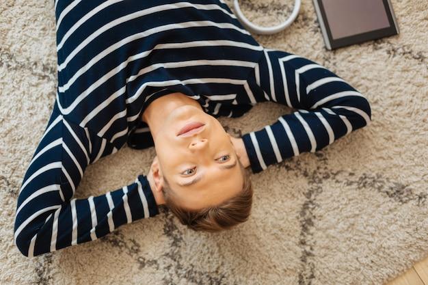 Отдых на полу. красивый сосредоточенный светловолосый хорошо сложенный молодой человек, лежащий на полу и думающий, а его планшет лежит рядом с ним
