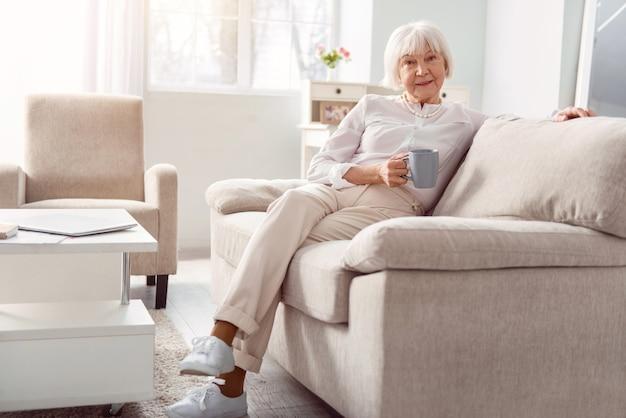リラックスした娯楽。ソファに座って、背もたれに快適に寄りかかって、コーヒーのカップを押しながらポーズをとる小柄な年配の女性