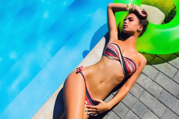 Relaxing poolside. awesome tan beautiful young woman in bikini lying by the pool and relaxing in stylish swimwear.