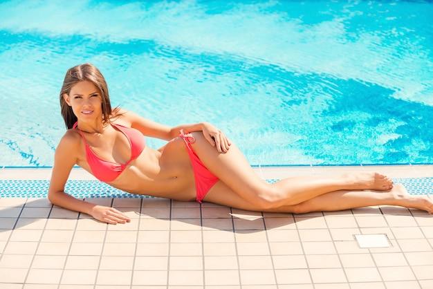 편안한 풀사이드. 수영장 옆에 누워 웃고 있는 비키니 입은 아름다운 젊은 여성의 전체 길이